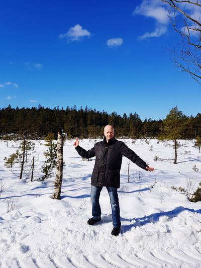 Full length portrait of man standing on snow field