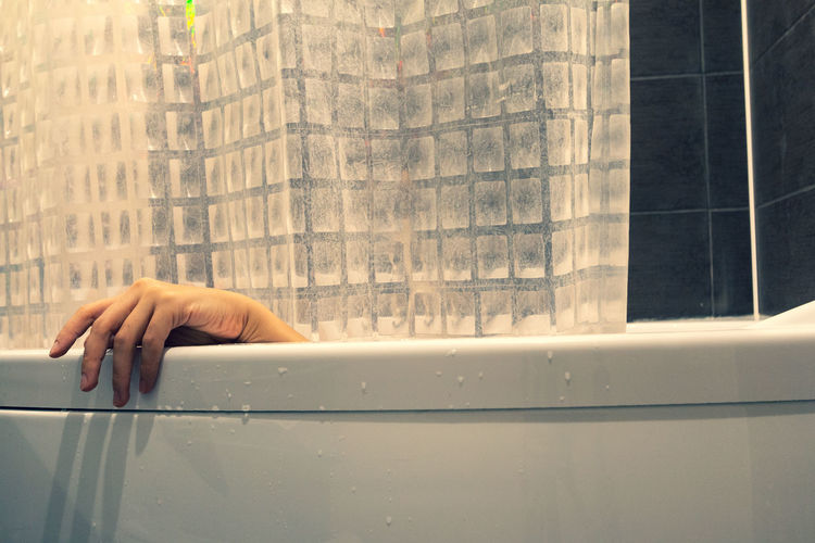 Cropped hand in bathtub