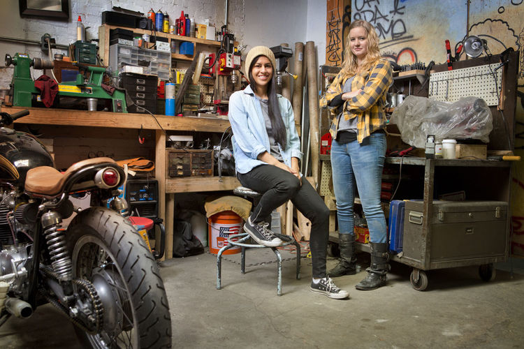 Portrait of happy female owners in auto repair shop
