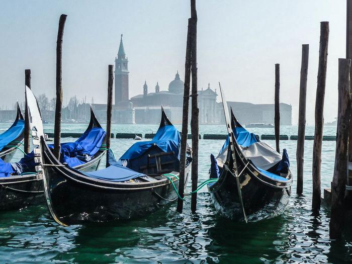 Gondolas moored in grand canal by santa maria della salute