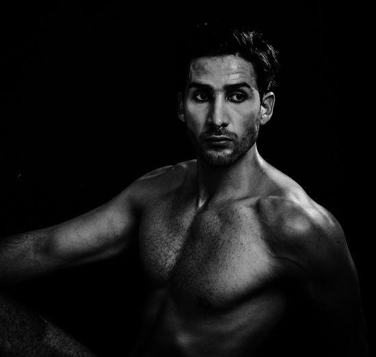 Muscular man looking away against black background