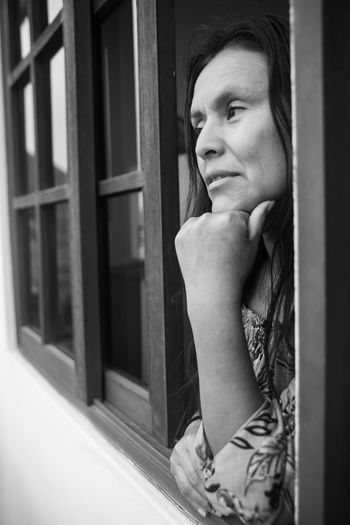 Portrait of woman looking away while standing against window