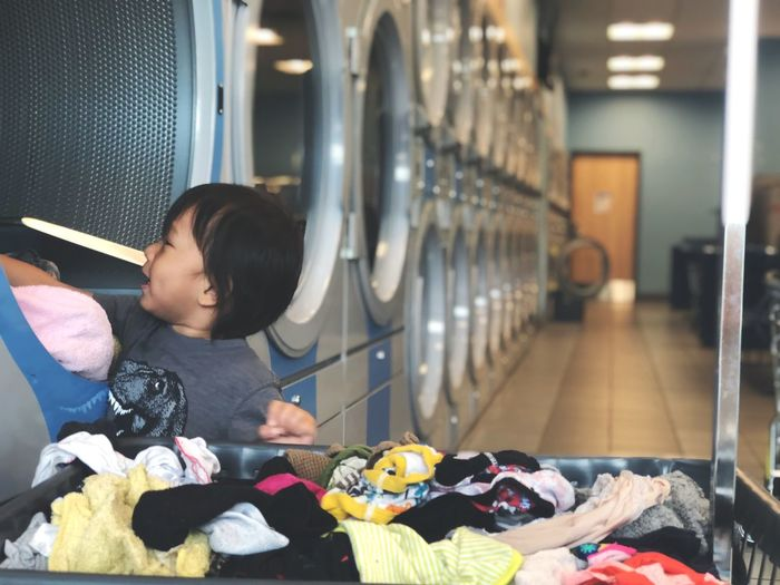 Close-up of boy putting laundry in washing machine in laundromat