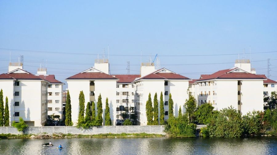 Houses by river and buildings against clear sky