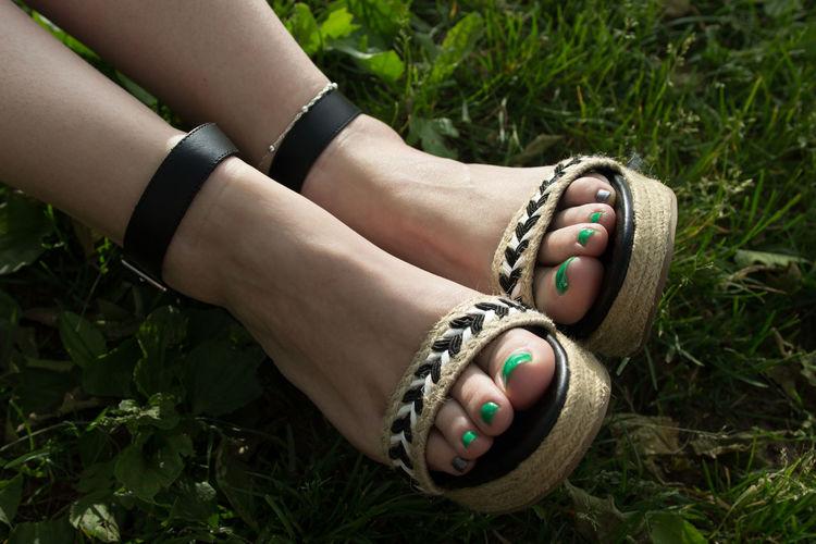 Low Section Of Woman Wearing Sandal On Field