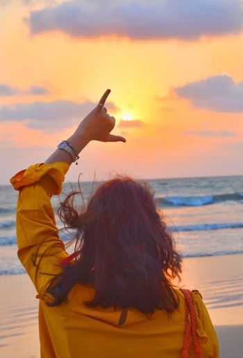 Rear view of woman gesturing shaka sign at beach during sunset