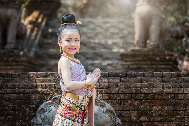 Portrait of smiling girl with hands clasped against temple