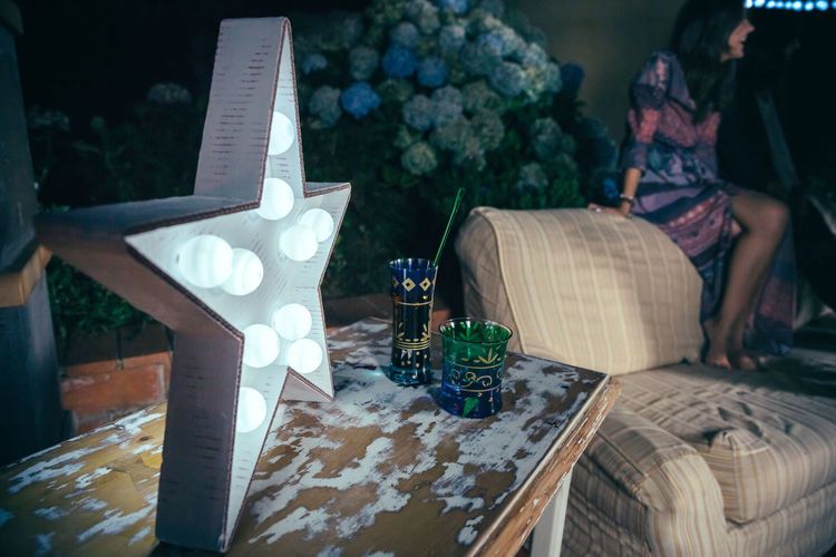 Drinks And Star Shaped Light On Table Against Woman Sitting On Sofa During Party