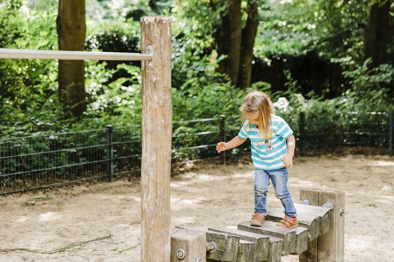 Full length of girl standing on play equipment at park