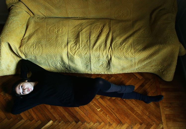 High Angle View Of Woman Lying On Floor By Sofa At Home