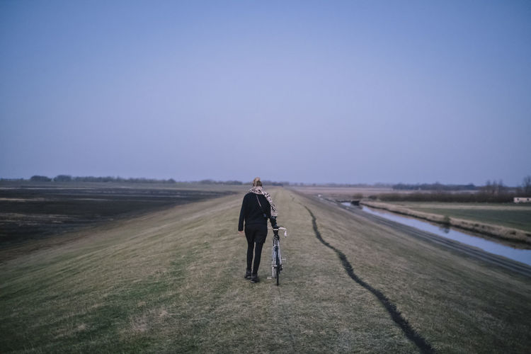 Rear view of man walking on field against clear sky
