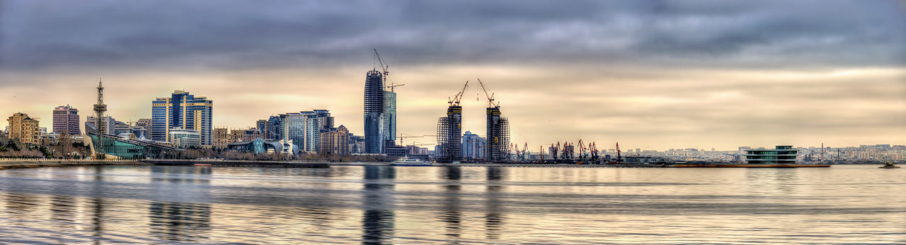 City buildings by river against cloudy sky