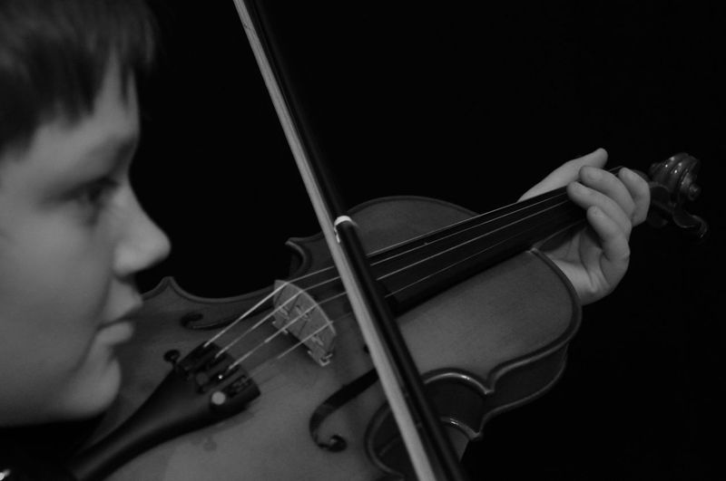 Man looking away while playing violin against black background