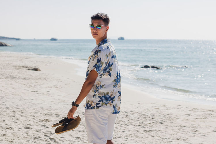 Portrait Of Man In Sunglasses Walking At Beach Against Sky
