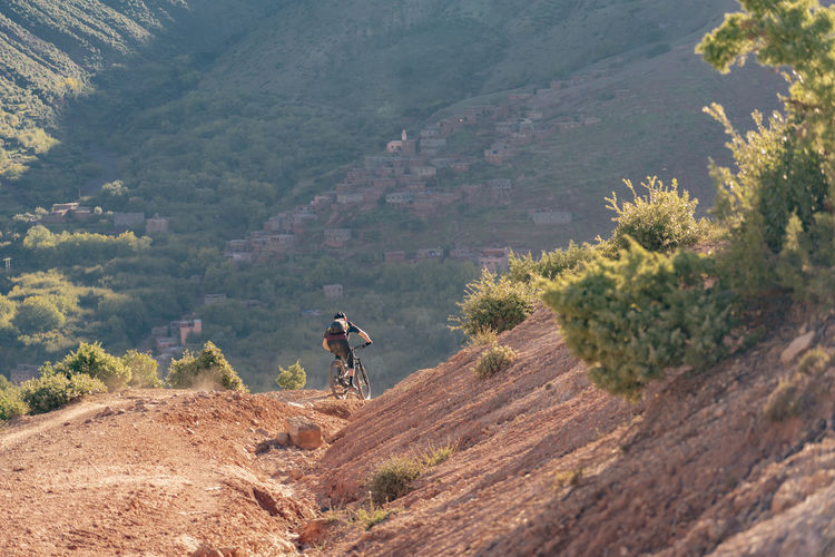 Mountain One Person Landscape Leisure Activity Adventure Lifestyles Activity Mountain Range Adult Outdoors Mountain Bike Mountain Biker Mountain Biking Red Clay Red Dirt Village Valley Golden Hour Sunset Morocco Descending Fast Speed Sport Riding