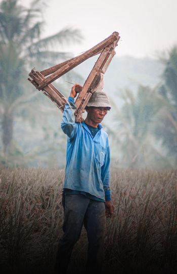 Man holding umbrella on field
