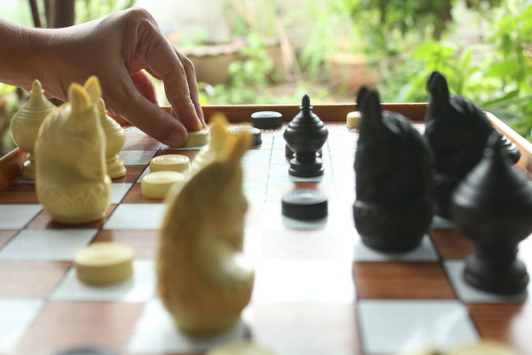 Cropped Hand Playing Chess By Window