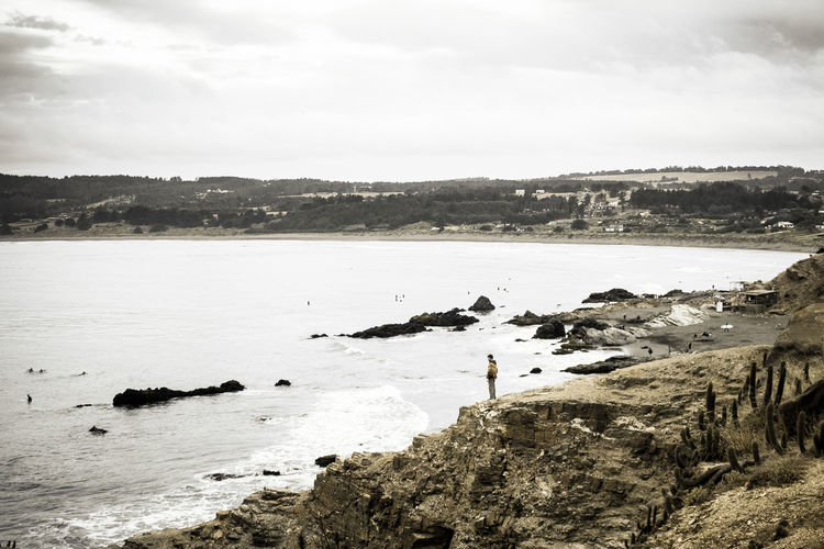 Distant view of person standing on cliff by sea against cloudy sky