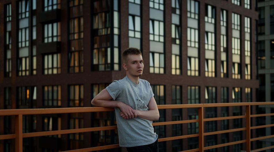 Full length of young man standing by window