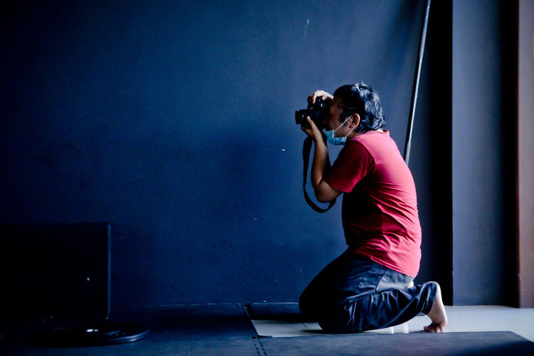 Man photographing while sitting against blue wall