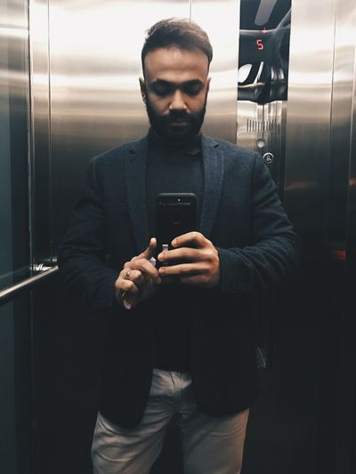 Portrait Of Man Taking Selfie While Standing At Elevator