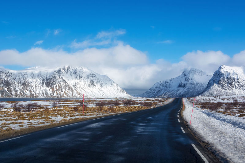 Road amidst snowcapped mountains against sky during winter norway
