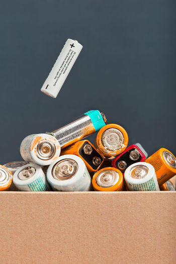 Close-up of battery in container against colored background