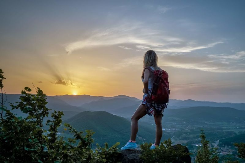 Rear view of woman standing on rock against mountains and sky