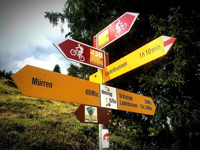 Where next? Decisions Summer Switzerland Berner Oberland Mürren Lauterbrunnen Red Yellow Destination Travel Adventure Direction WhichWay Biking Hiking Signpost Text Number Communication Guidance Day No People Outdoors