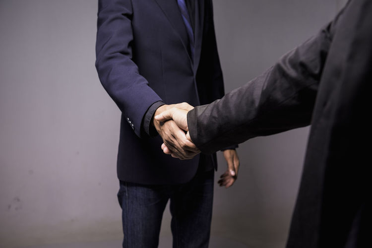 Midsection of businessmen shaking hands on gray background