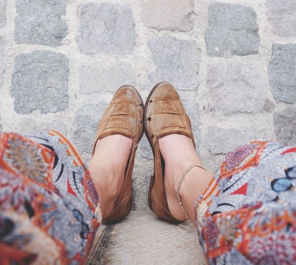 Low section of woman in flat shoe relaxing on street