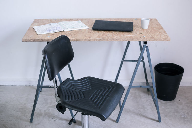 Empty chair by laptop on desk in office
