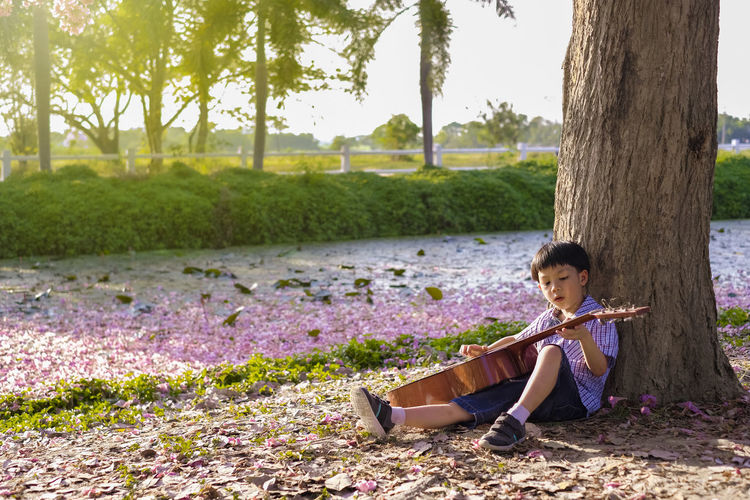 Boy playing guitar while sitting in park