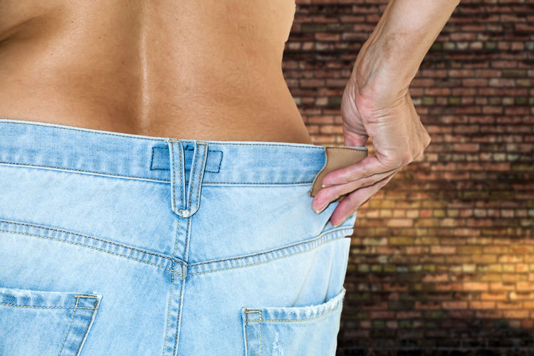 Midsection of woman wearing jeans at home