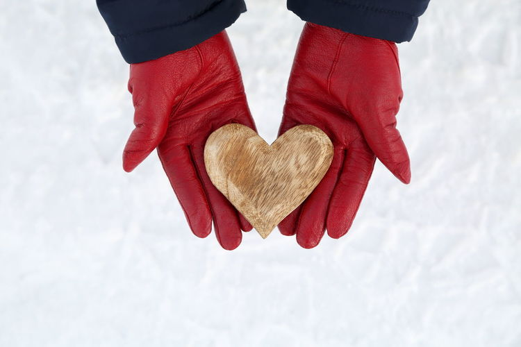 Low section of woman holding heart shape in winter