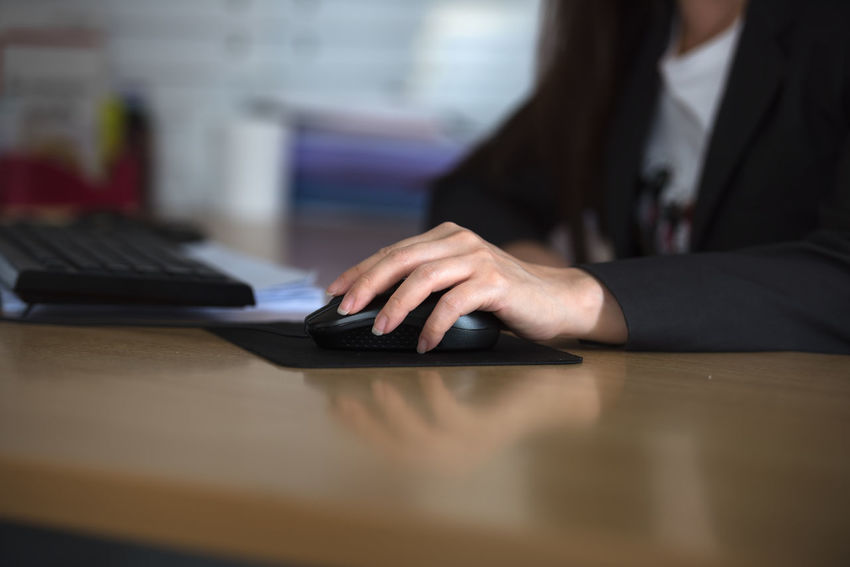 business woman hand with mouse. Shallow depth of field. Selective focus. Close-up Computer Computer Keyboard Day Desk Human Body Part Human Hand Indoors  Keyboard Laptop One Person People Real People Table Technology Using Laptop Wireless Technology Women Working Young Adult