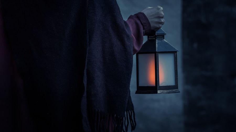Close-up of hand holding an illuminated light lantern
