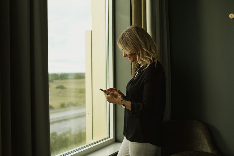 Woman looking through mobile phone at window