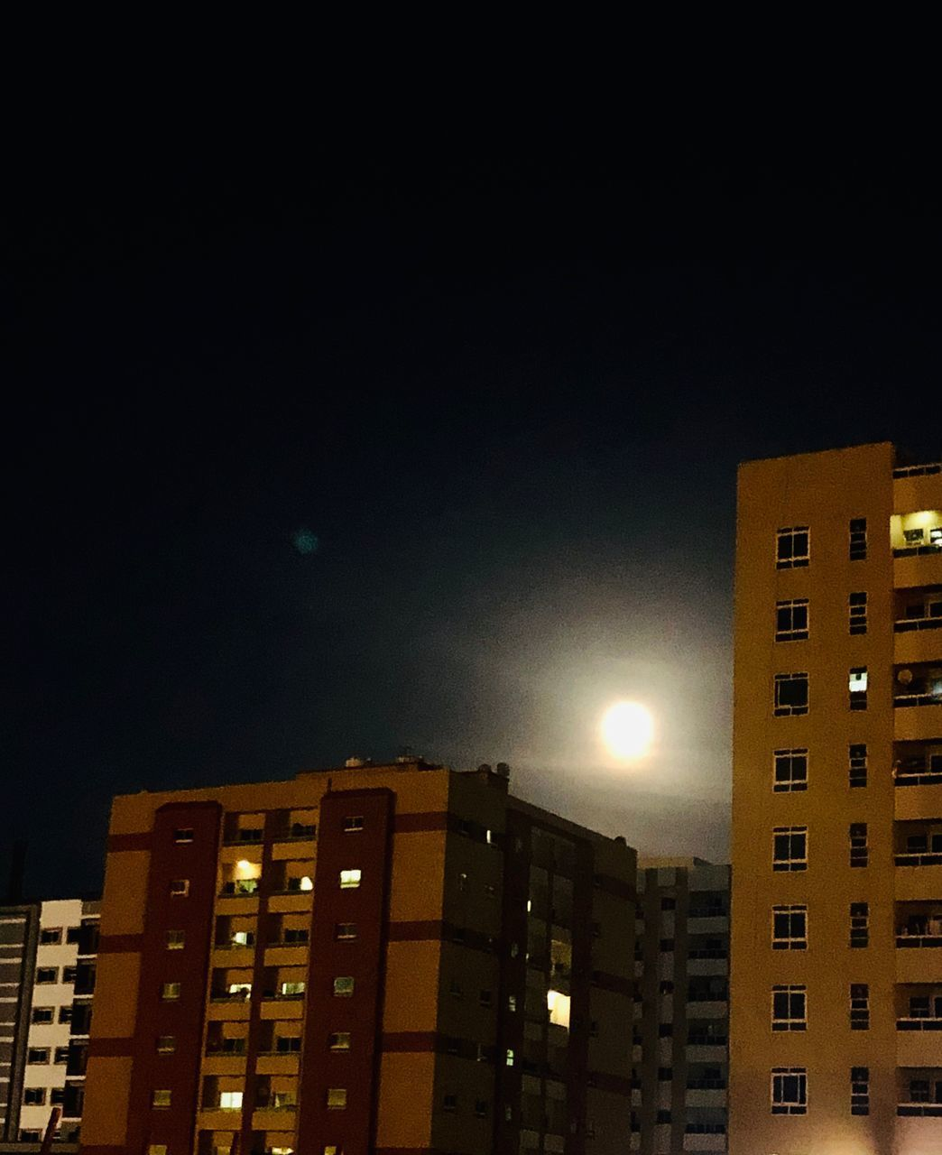 architecture, building exterior, night, built structure, building, city, sky, illuminated, low angle view, no people, copy space, moon, residential district, nature, outdoors, lighting equipment, clear sky, apartment, tall - high, office building exterior, skyscraper, moonlight