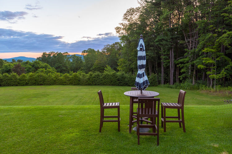 A view of a table and chairs while dusk settles over the Berkeshires in the background Berkshires, Dusk Sky Rolling Hills Calm, Rest, Quiet, Peace, Silence, Tranquility Chairs And Tables Countryside Outdoor Dining Outside Eating Pastel Colors Rural Landscape Table