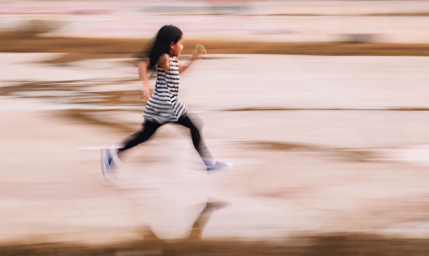Healthy Lifestyle Girl Playful Running One Person Motion Blurred Motion Full Length Hair Young Adult Leisure Activity Striped Casual Clothing Long Hair Young Women Hairstyle Day Black Hair Water Outdoors Childhood Child