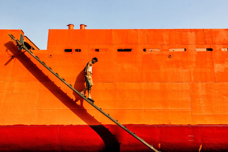 Side view of man walking on ladder by wall against sky