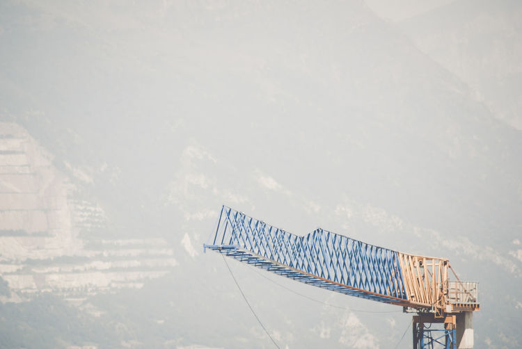 Jib of tower crane against mountain in foggy weather