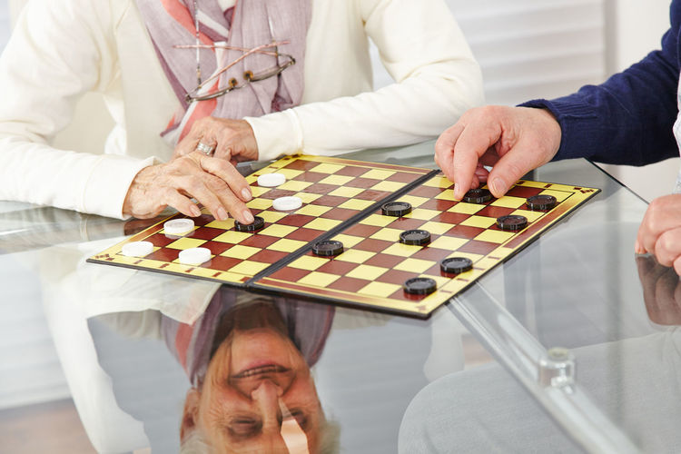 Senior couple playing checkers at table