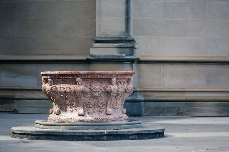 Old carved pedestal on street against wall