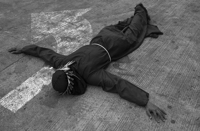 Low section of man sleeping on sidewalk
