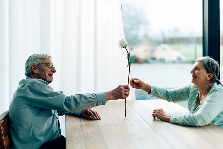 Love at seventy. happy man hands a rose to his wife. smiling elderly couple sitting together