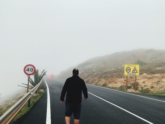Rear view of man walking on road against sky during foggy weather