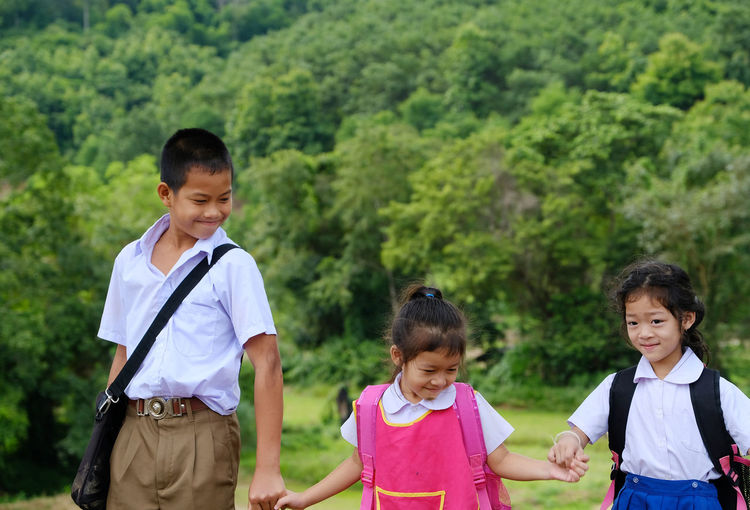 Siblings in school uniforms holding hands while standing against trees