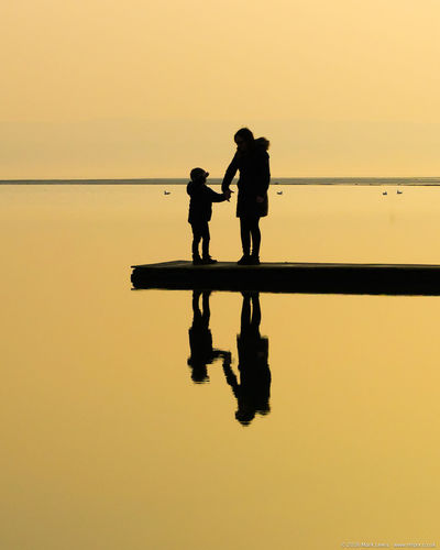 Mother standing with son by lake during sunset